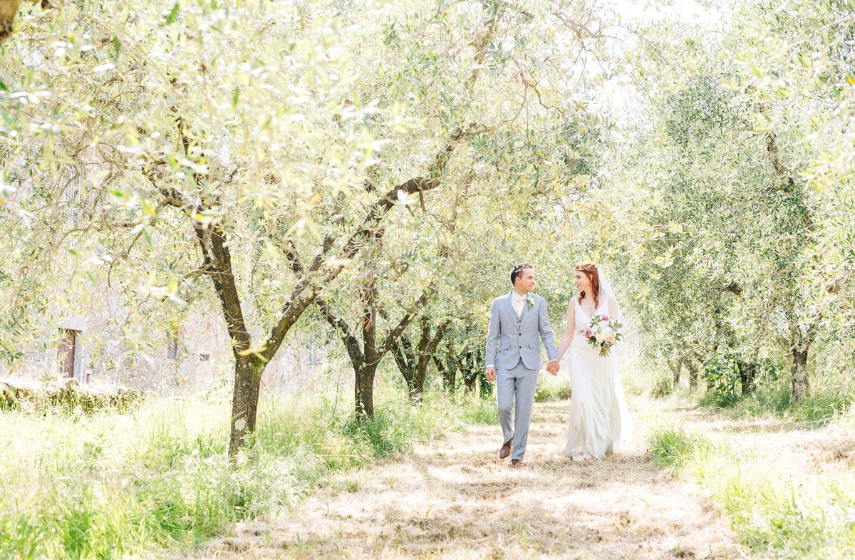 Newlyweds walking through the olive tree groves in Tuscany